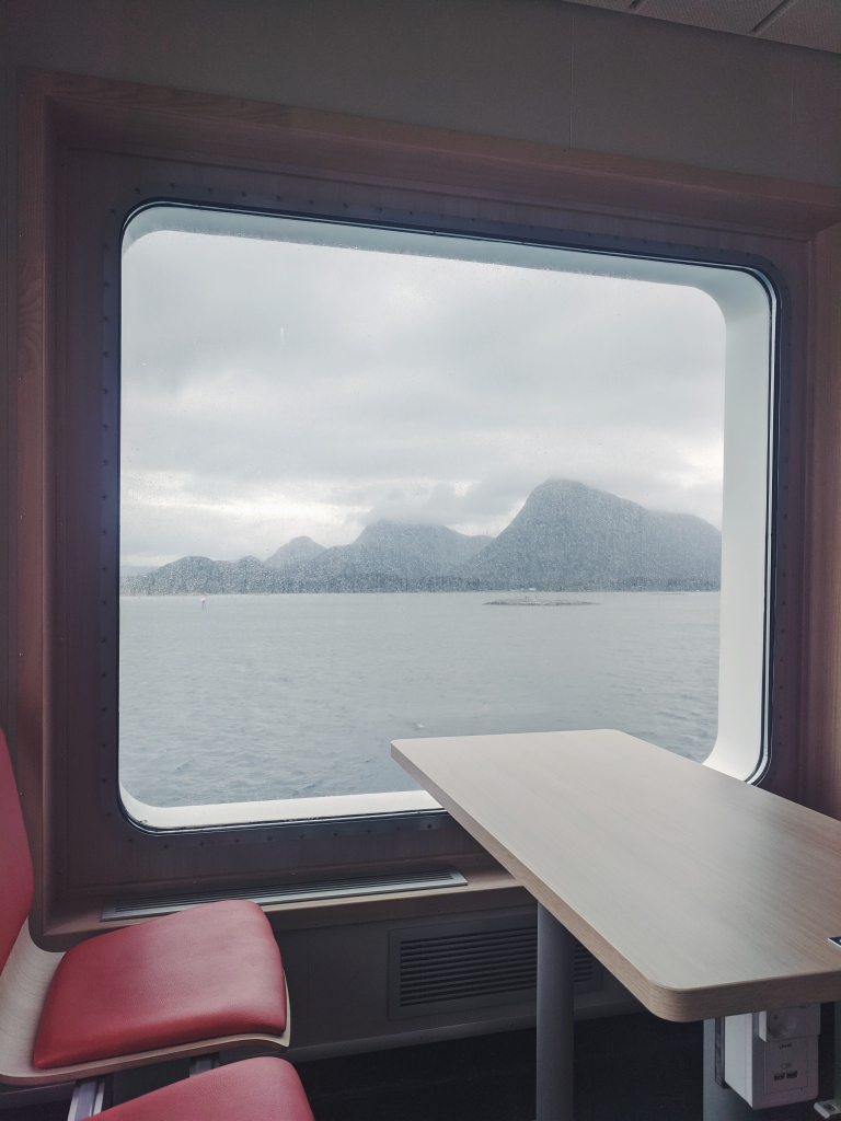Mountains and water are visible through the window of a ferry boat. A table and red seats are visible in the foreground.