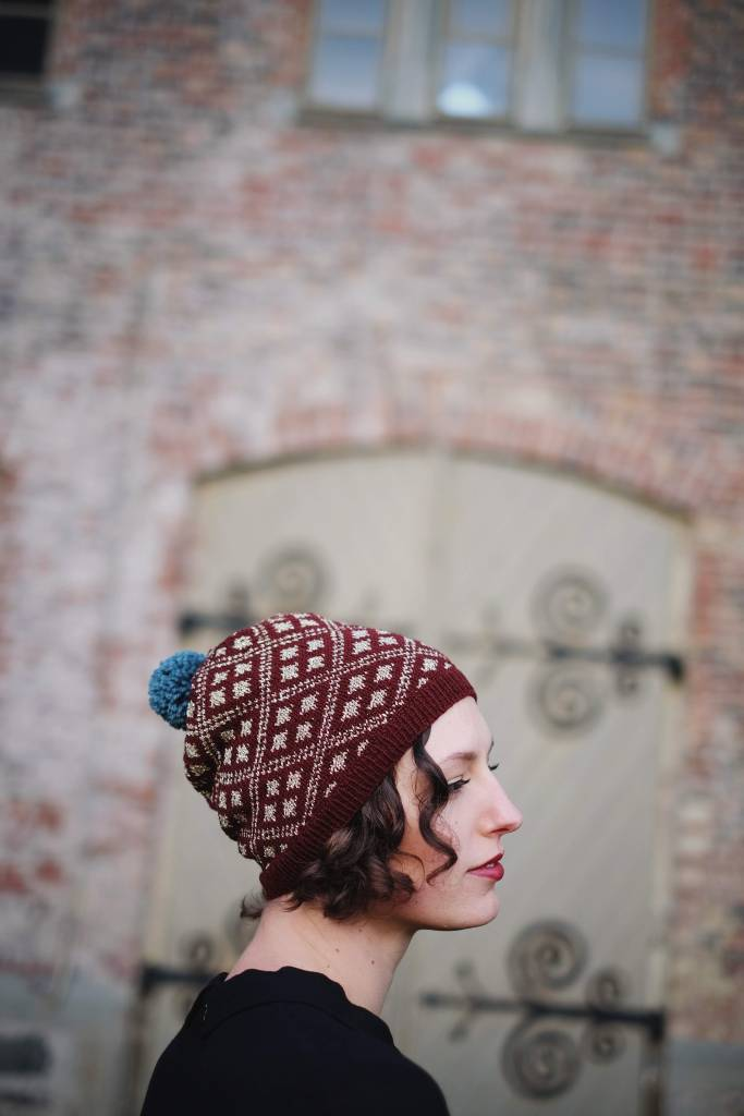 Dianna wears a burgundy and gold hat with a pattern of colorwork diamonds while standing in front of an old brick wall and set of doors with fancy ironwork.