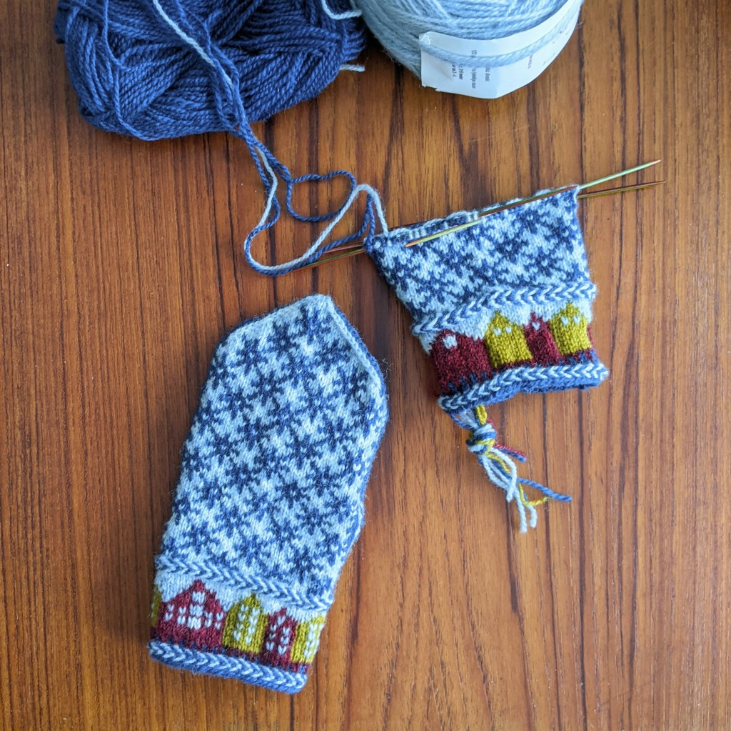 A pair of mittens in progress lays on a warm wooden table. The mittens are blue, red, and yellow, with a pattern of buildings around the cuff. One mitten is only half-finished.