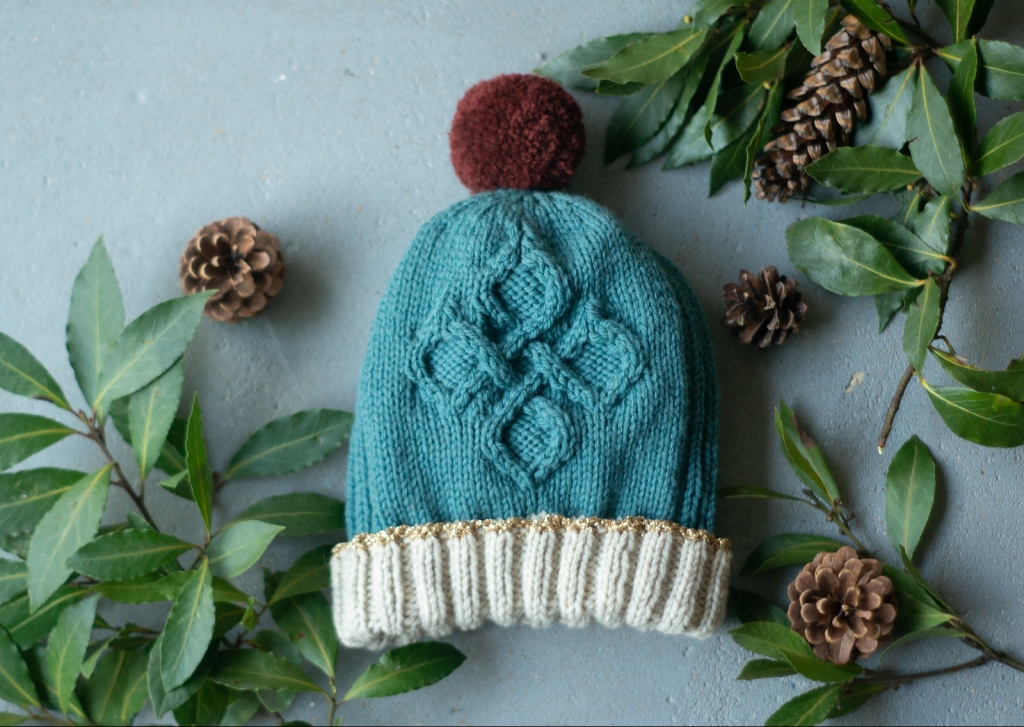 A knitted hat featuring a diamond cable pattern in tealy blue with off-white trim and a burgundy pom pom lays on a grey floor surrounded by leafy branches and pine cones.