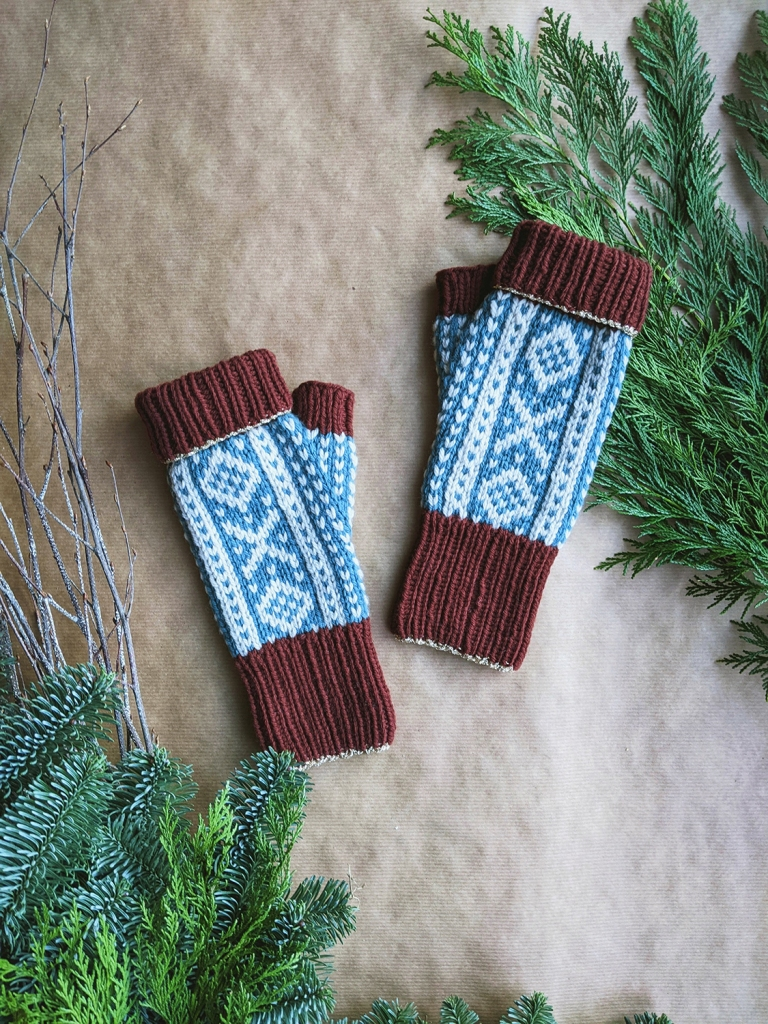 A pair of colorwork fingerless mitts in shades of burgundy, off-white, and blue laid out on brown paper with evergreen branches arranged around them.