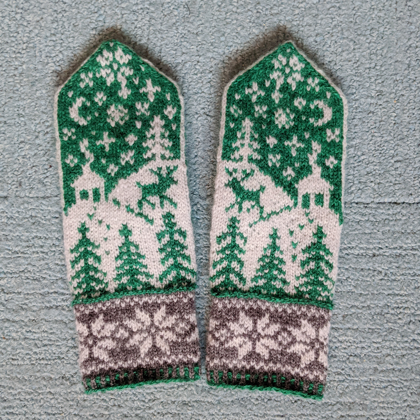 A pair of mittens in green, white, and grey lays on a carpet. The mittens feature a wintry scene with trees, falling snow, a little house, and a reindeer.