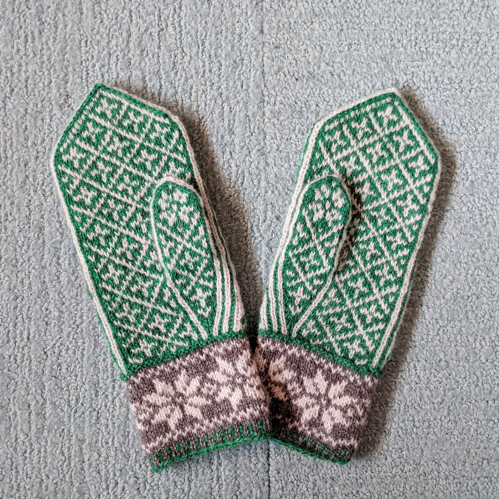 A pair of mittens in green, white, and grey lays on a carpet, palm side up. A geometric pattern of diamonds covers the palm and thumb.