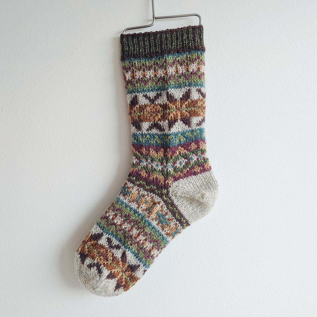 A Fair Isle sock in shades of brown, green, blue, white, orange, purple, and yellow hangs against a white wall.