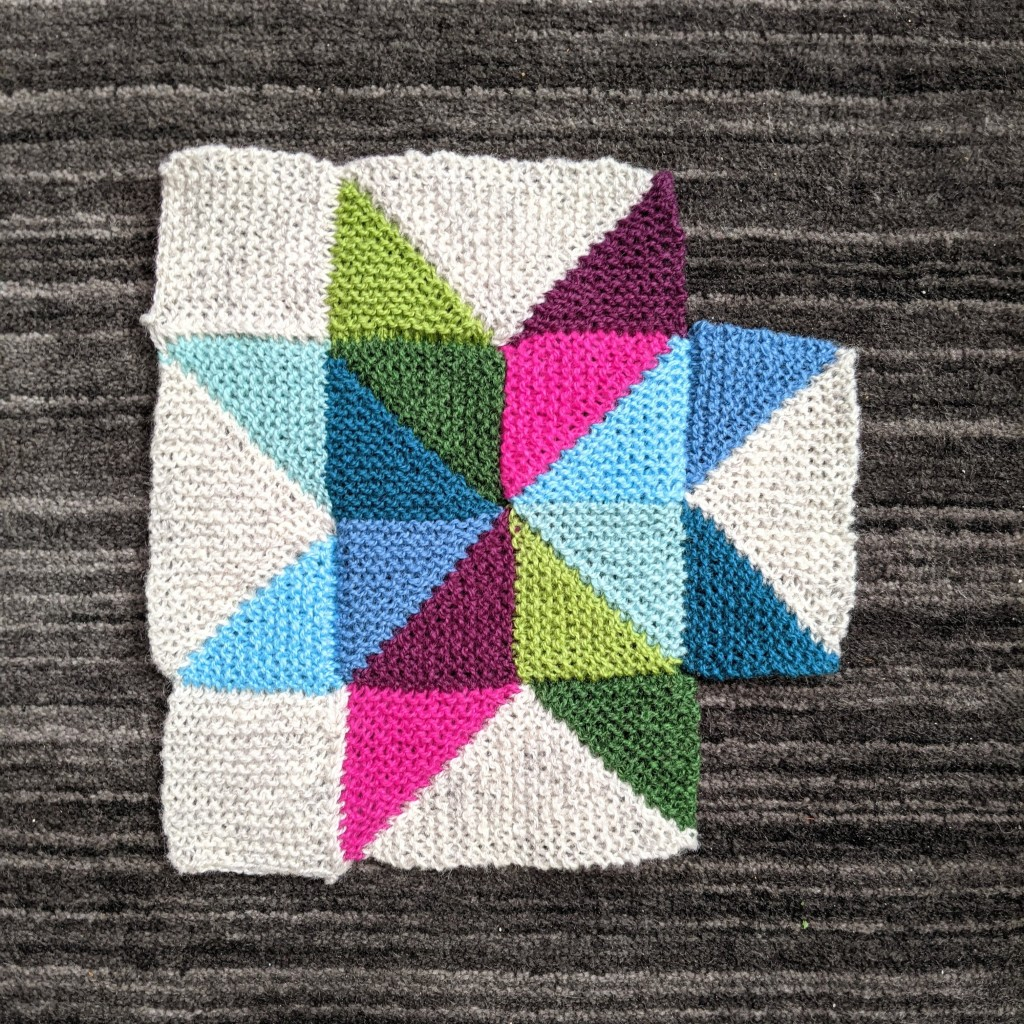 A multi-colored eight-pointed star knitted in garter stitch lays on a dark grey carpet.