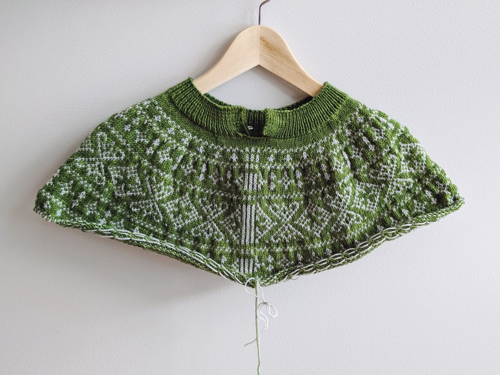 The yoke of a cardigan in progress sits on a hanger against a grey wall. The cardigan yoke is grass green with light grey colorwork.