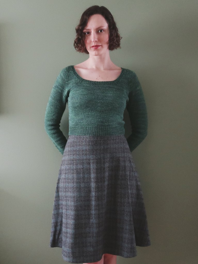 Dianna stands against a grey-green wall, wearing a green knitted top and a skirt in a subtle plaid in shades of grey, blue, and brown.