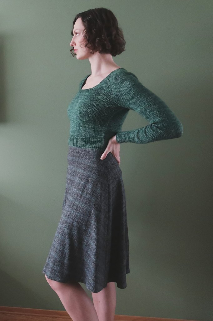 Dianna stands in front of a grey-green wall, facing left, and wearing a green knitted top and a skirt in a subtle plaid in shades of grey, blue, and brown.
